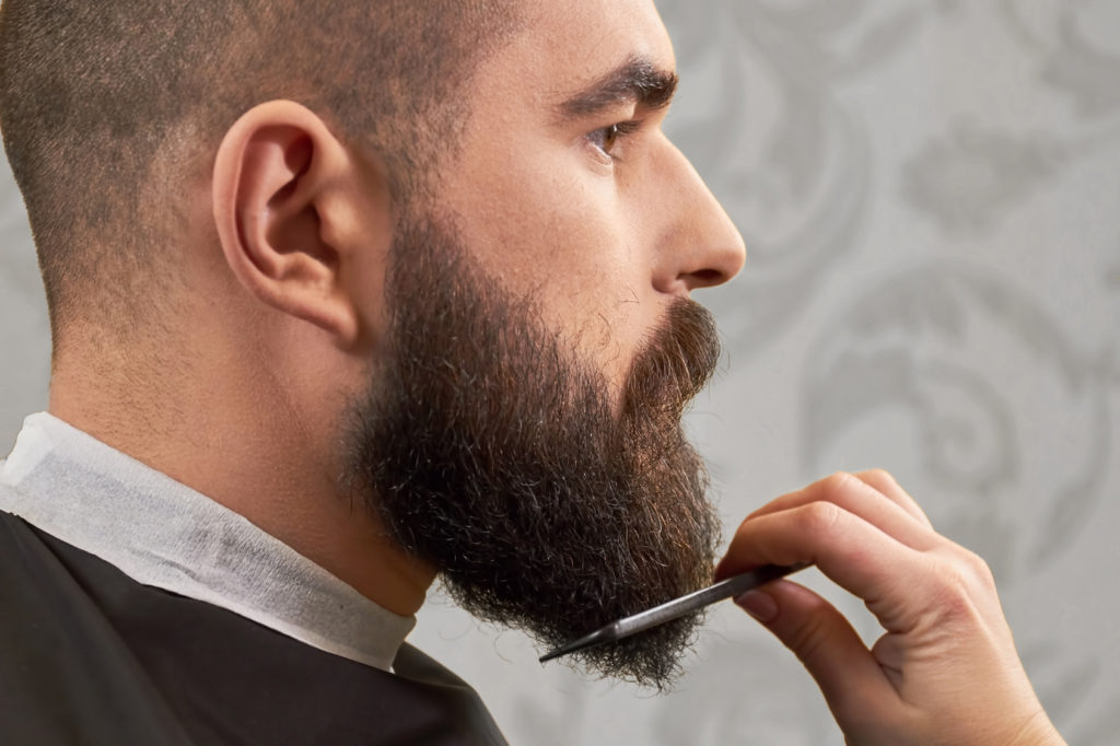 Side view of beard grooming. Hand of barber using comb.