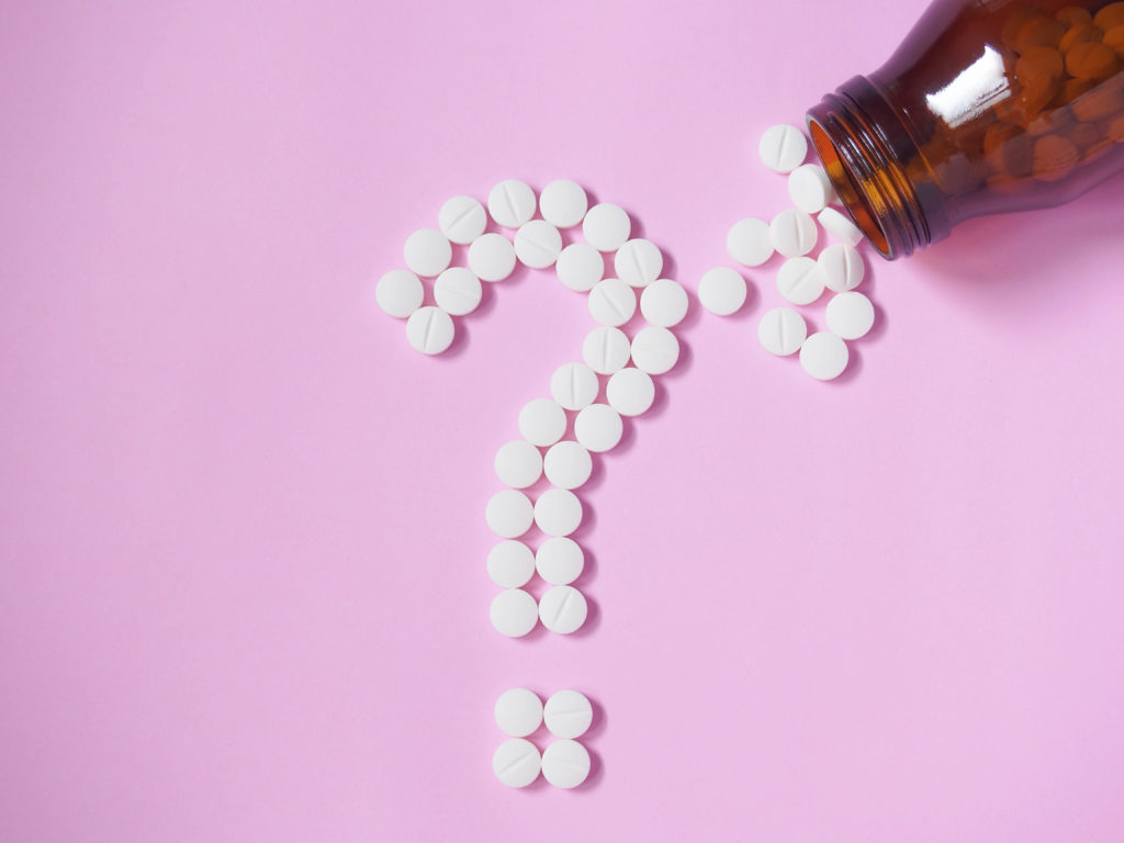 Question mark made by white pills spilling out of brown glass bottle on pink background. Creative medicine for health/medical problem, drug interaction, medication error and pharmaceutical concept.