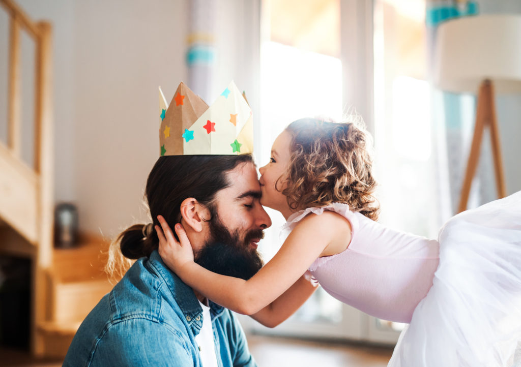 A side view of small girl with a princess crown and young father at home, kissing when playing.
