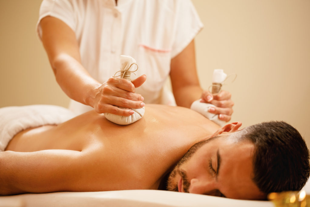 Young man enjoying in relaxing back massage with herbal balls at health spa.