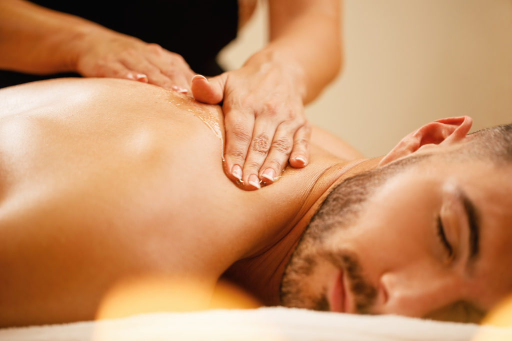 Close-up of man enjoying in relaxing back massage with honey at the spa.